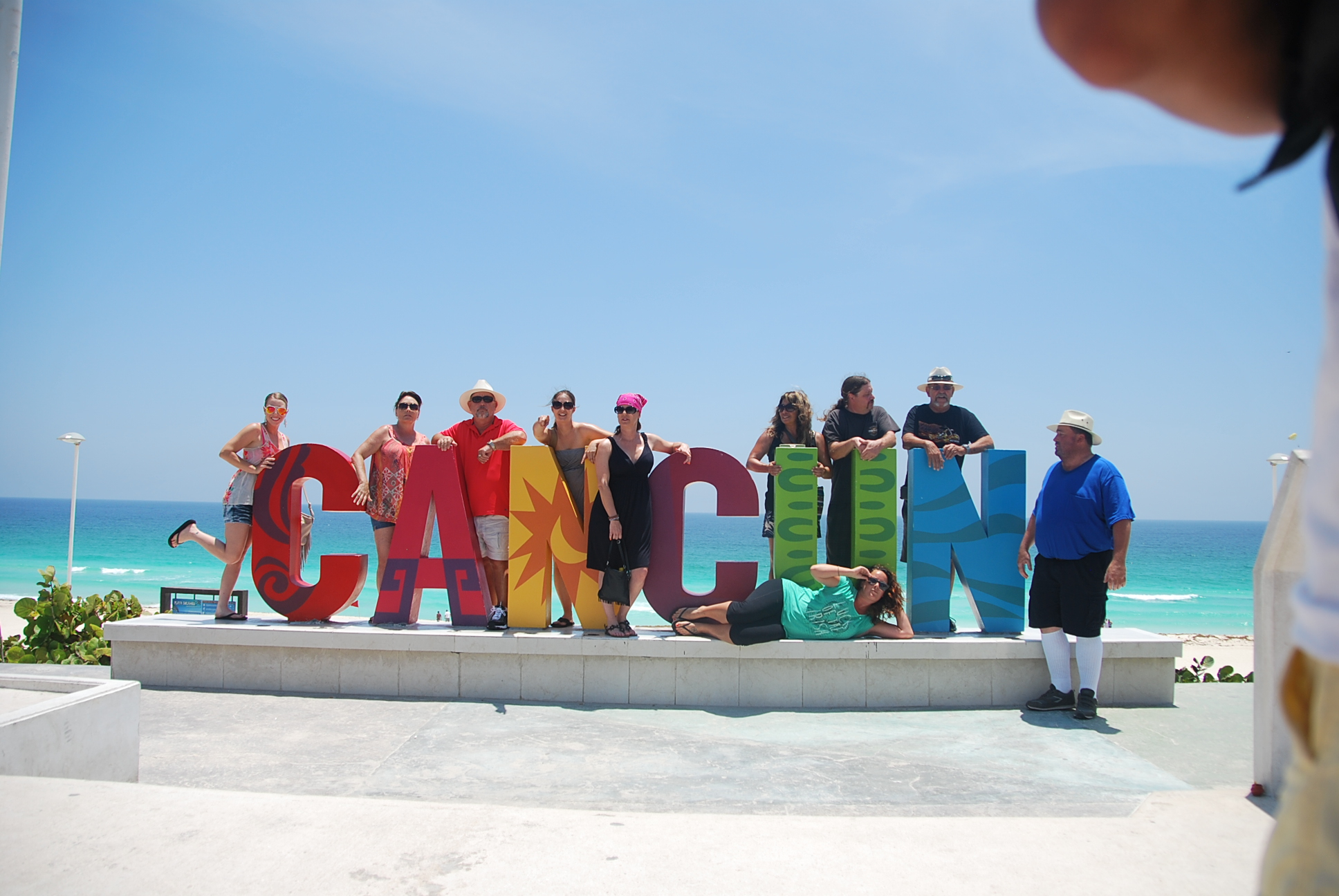 people standing by the Cancun sign