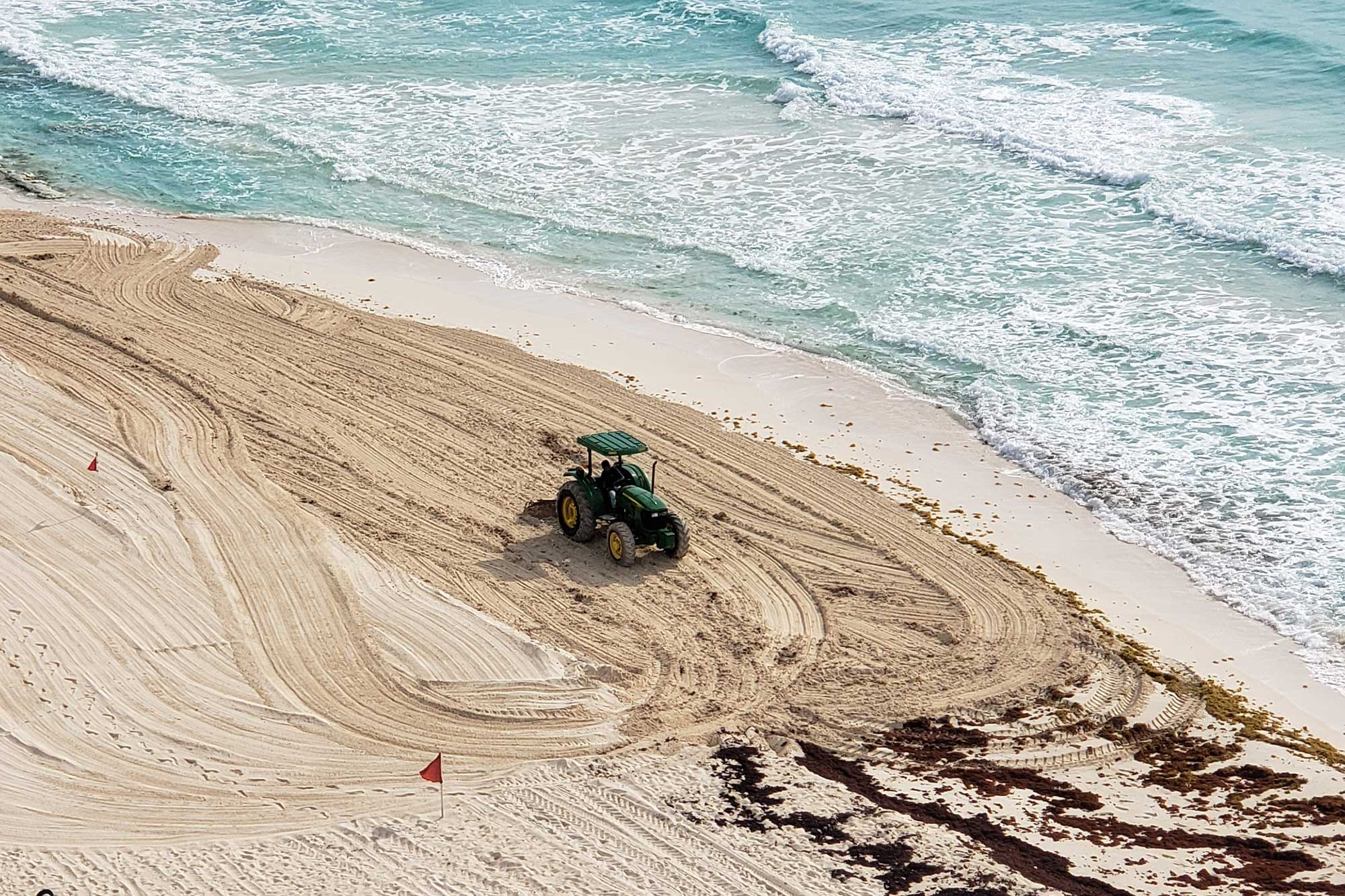 tractor cleaning the beach in cancun