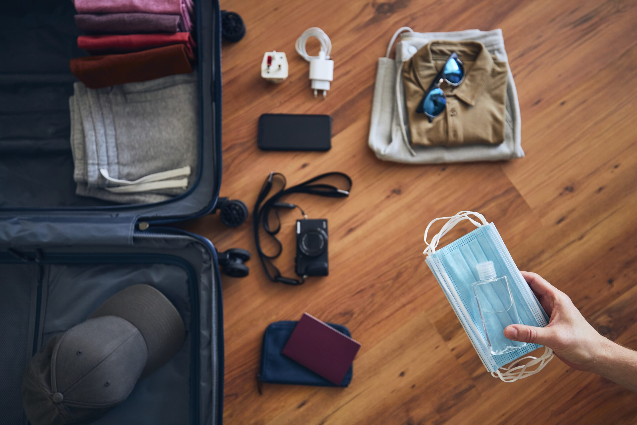 Traveler is preparing for travel in new normal. Hand holding face masks and hand sanitizer for personal protection against packing suitcace with summer clothing, passport and camera.